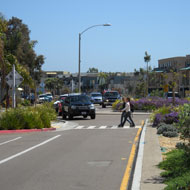 Roundabouts and medians help create pedestrian friendly short sidewalks. Source: MIG