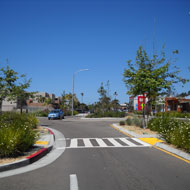 Traffic calming elements include well landscaped medians, bulbouts and roundabouts.Source: MIG